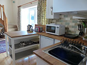 itchen area with sink, fridge, microwave, hob and toaster.