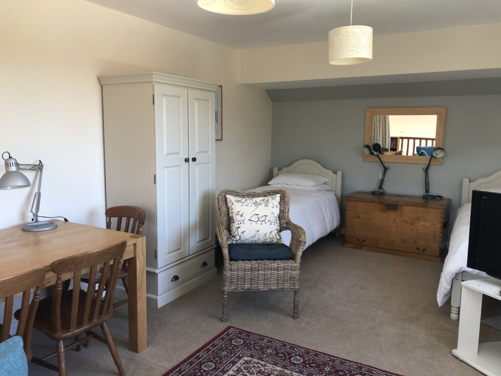 Twin beds upstairs and lounge area with desk.